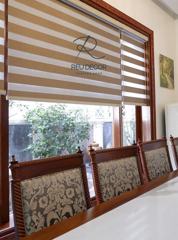 Cửa số phòng ăn được sử rèm cầu vồng có màu cam gỗ tương đồng với bộ bàn ghế, tạo cảm giác gần gũi